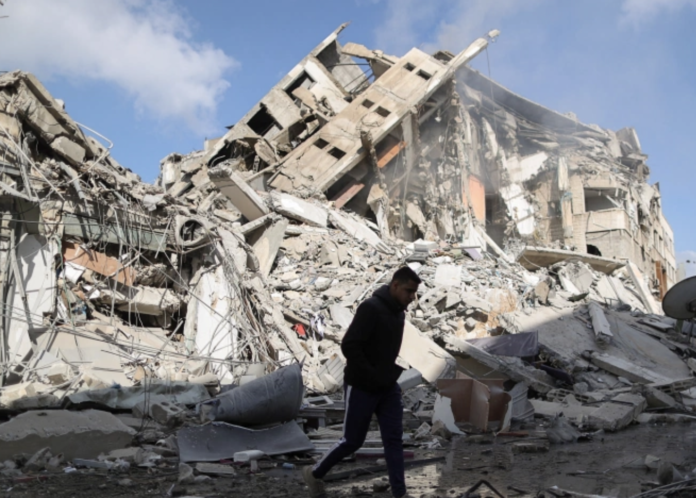 A Palestinian man walks past the remains of a tower which was destroyed by Israeli air strikes in Gaza City